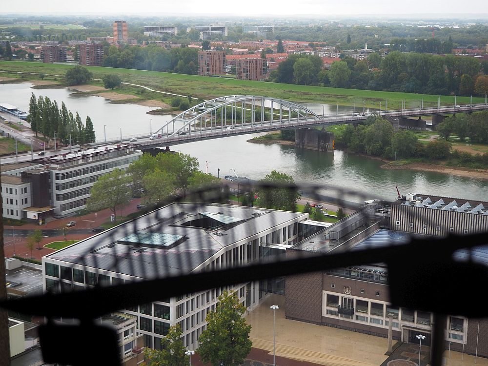 The river crosses the picture, and the arched bridge crosses the river. In the foreground is a blurry outline of the bridge -- a decal on the tower window. Below on the near bank of the river are recent buildings, as well as in the distance on the far side of the river.