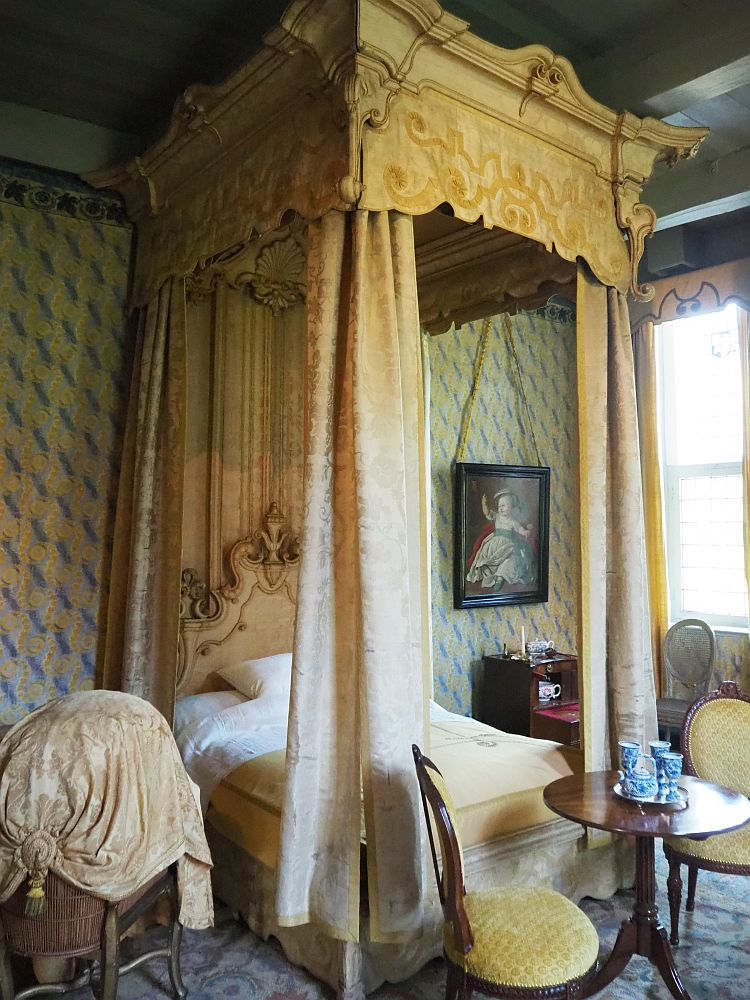 This photo is vertical of necessity because the roof of the four-poster bed reaches the high ceiling. The woodwork at the top as well as the curtains at each corner are pastel yellow. The headboard of the bed is partly visible and is ornately carved, also painted yellow. The wall behind had yellow wallpaper (or silk?) with a pattern of blue on it. Next to the bed is a small cupboard and a painting of a child hangs above it. At the foot of the bed is a simple round table with two upholstered yellow chairs and a small tea set in its middle.