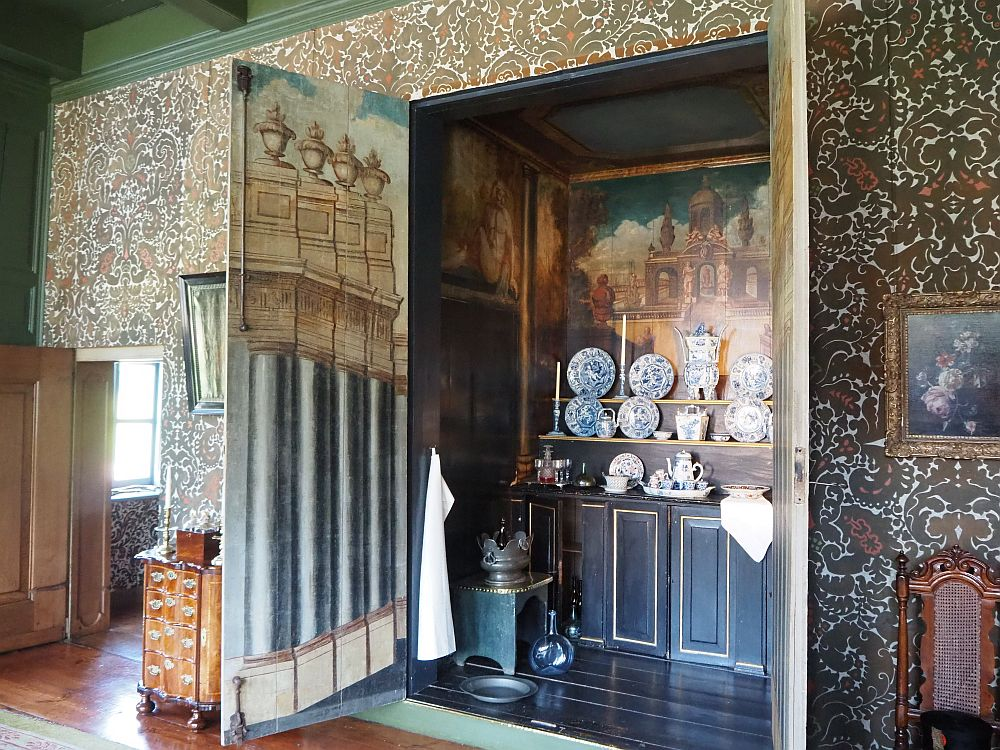 The doors to the buffet (more like a big closet) open outwards. Inside is a sideboard, with cabinets below and shelves above, covered with a blue and white porcelein set. The walls of the inside of the closet and the insdes of the door are painted with classical scenes: some sort of arched building on the back wall and large columns on the door.