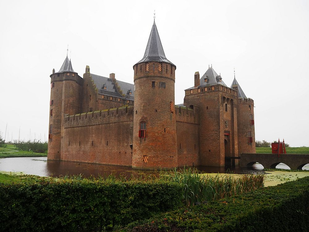 A view of Muiderslot Castle as seen from one of the four corners. The nearest tower is round with a pointed roof. The walls are red brick and it sits in the middle of a moat. bridge is visible on the right leading to a square gate.