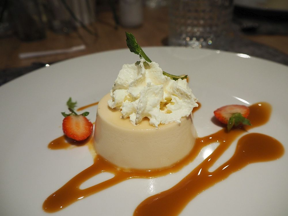The panna cotta is perfectly formed from a round mold. It has a bit of whipped cream on top, two halves of a strawberry beside it, and a dribble of caramel sauce.