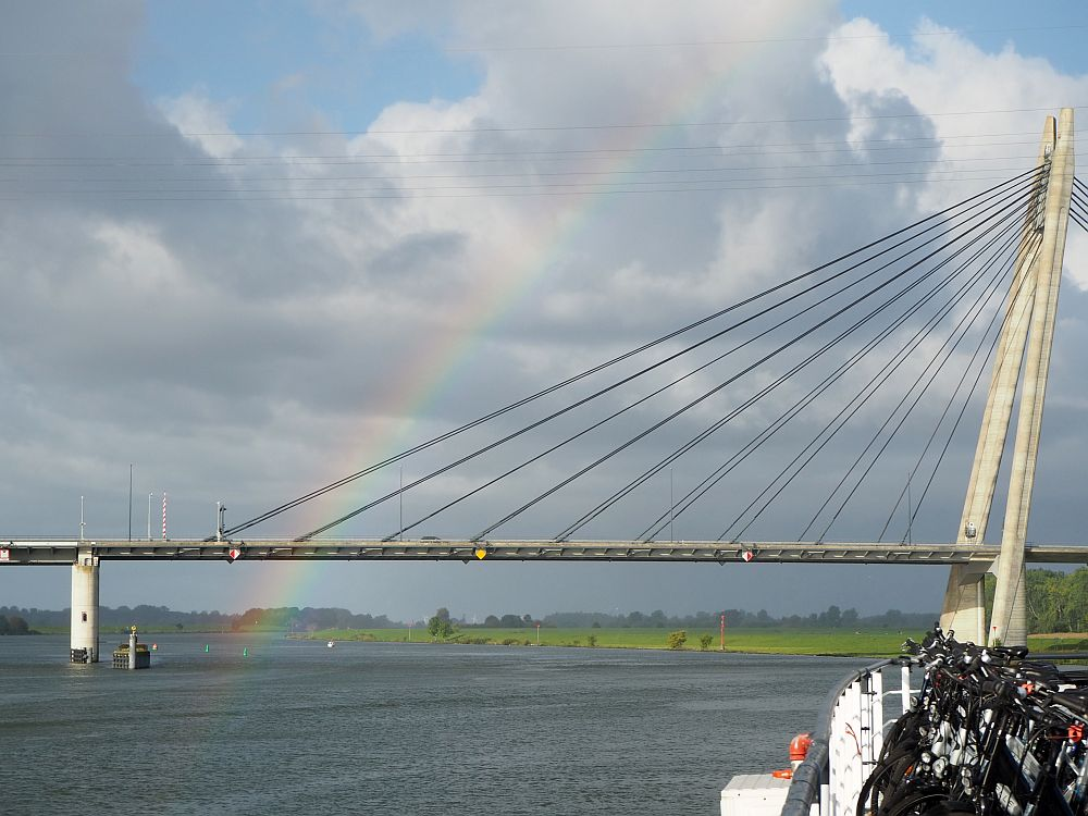 Part of a suspension bridge crosses the picture, with a rainbow visible against the clouds.