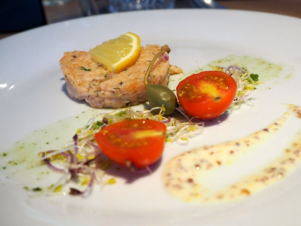 A dollop of salmon with a slice of lemon on top. Next to it, two halves of a cherry tomato, a fresh olive, and some sprouts. All of it is dribbled with dressing.