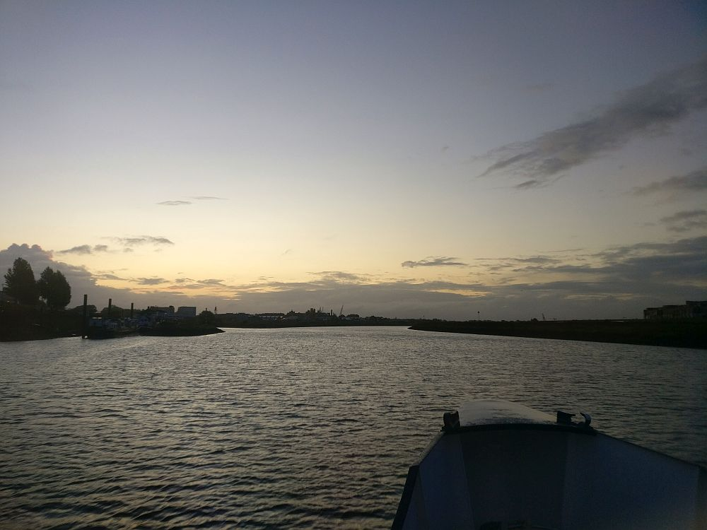 The bow of the boat for our boat bike tour in the foreground, in silhouette. Water ahead, with flat riverbanks in the distance, also in silhouette. The sky and clouds are lit up before the sunrise.
