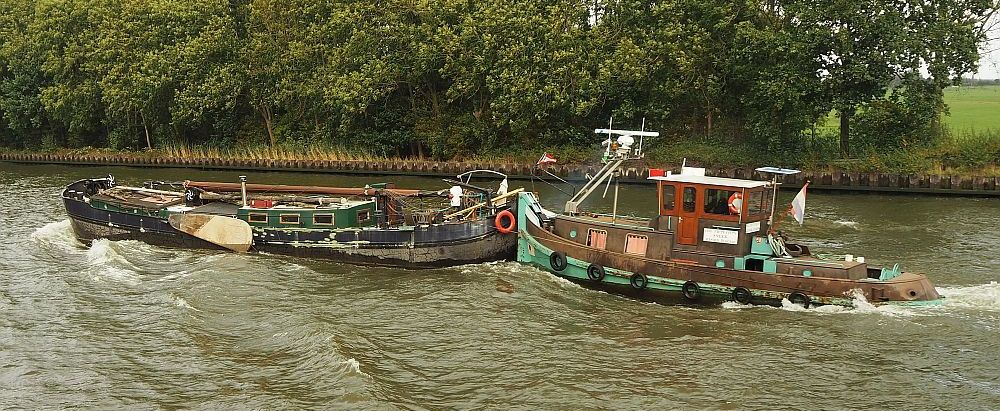 An old-fashioned little tugboat pushes another boat, which is a rundown-looking older wooden Dutch boat, the kind with sideboards. The mast is lying on top of it.