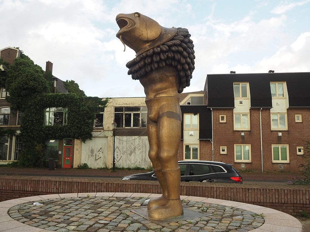 The statue has a human man's body but has no arms and the head is the face of a fish, while it wears a large bumpy ring around its shoulders.