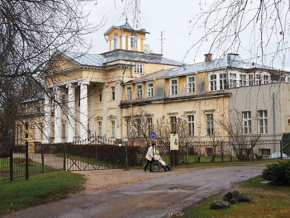 The mansion is light yellow and has classical columns in front of the main entrance, holding up a triangular pediment. The center part is 4 stories tall with a small square structure on the roof. The two wings are lower, just two stories. A woman pushes another woman in a wheelchair in front of the manor.