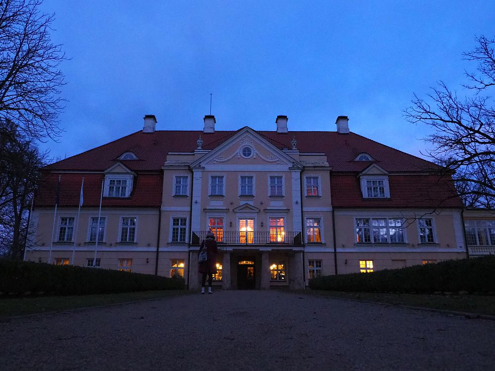 The symmetrical manor house is a pastel orange color with white edging and a reddish roof. It is four stories tall with a grand, decorative entrance. The sky is dark and lights blaze from the windows on the first two floors.