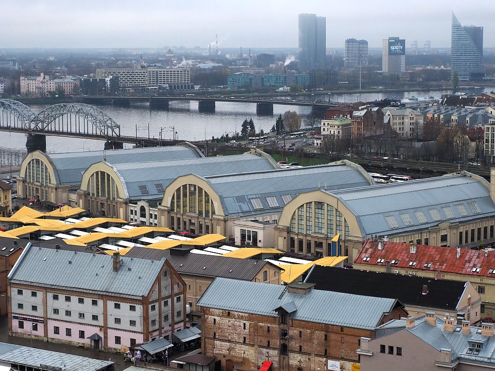 View from a high building shows the 4 half-cylindrical buildings in a row. In front are some rectangular brick buildins a few stories tall. Behind is the river and three bridges crossing it are visible. Low-rise buildings behind the market on this side of the river, a few high-rise buildings on the other side.