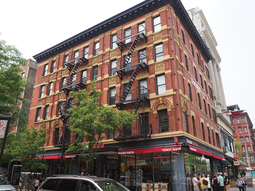 A corner building, red brick with decorative elements between and above the windows in white stone. Two black fire escapes zig-zag down one side of the building. The ground floor has a red awning that says Tenement Museum. Above the ground floor are four more stories.