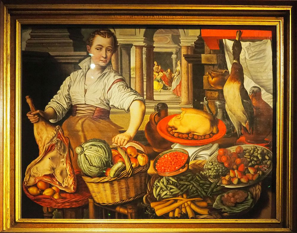 In the foreground of the painting is a woman hoding a leg of lamb and a basket of fruit and vegetables. The table is strewn with various foods. Behind is a gateway with columns and beyond that is a cluster of several people.