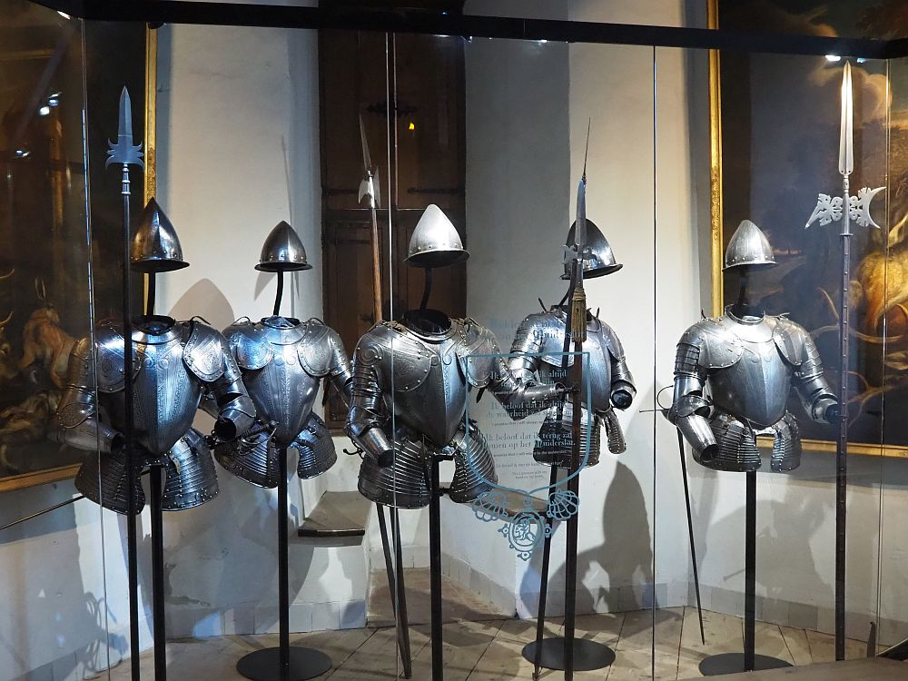 Five suits of armor stand on simple poles. Each has just the top half of a coat of armor: chest plates, arm protectors and helmets.