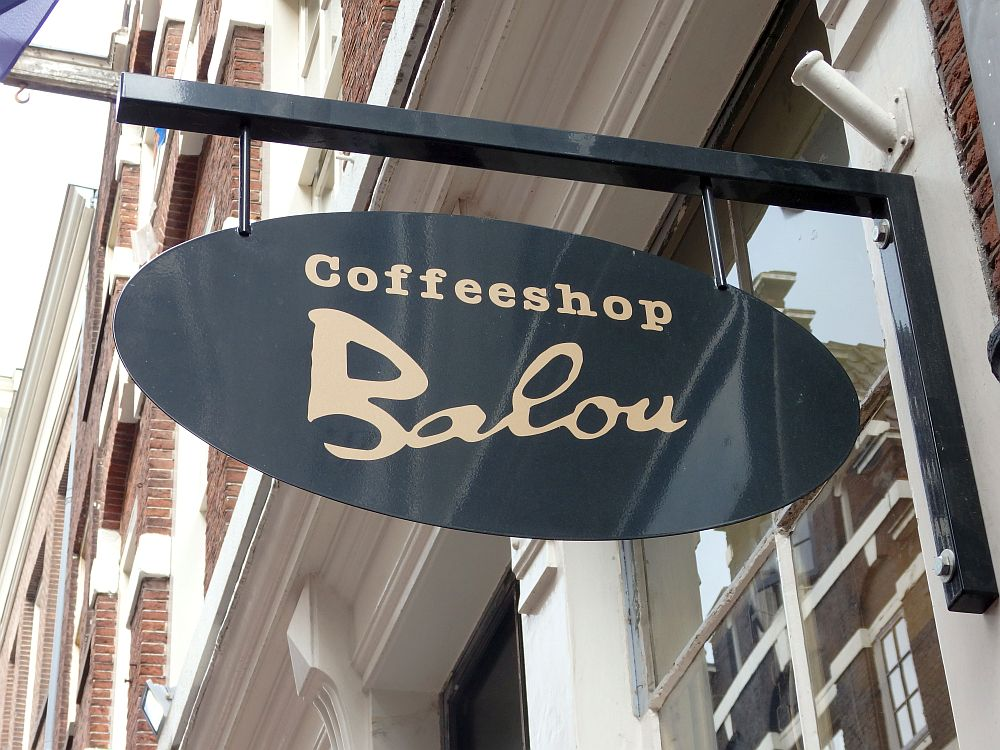 """An oval sign sticking out from a building reads """"Coffeeshop Balou"""""""