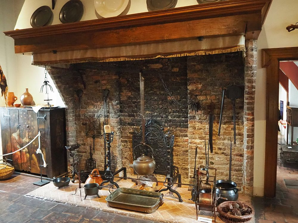 A plain brick fireplace with a wooden mantel above it. Inside it a number of kitchen utensils can be seen: copper pots and pans mostly.