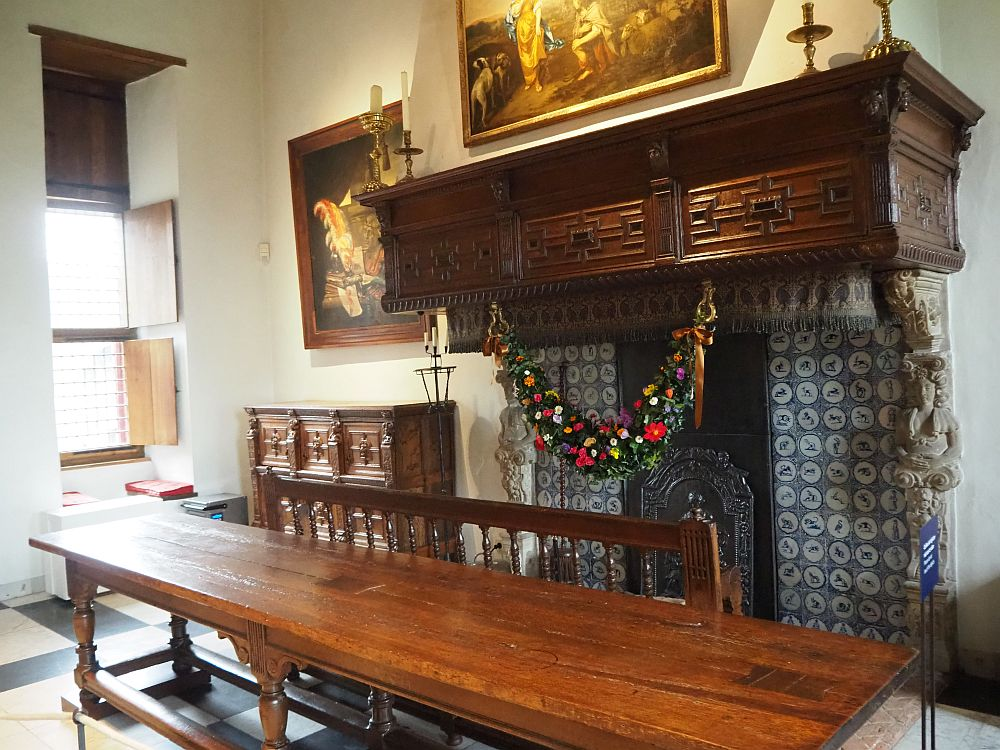 A dark wood mantelpiece over a fireplace lined with Delft tile, each end supported by a person carved in white stone. In front of the fireplace is a long wooden table with a long bench between it and the fireplace. Above and beside the fireplace are two paintings.