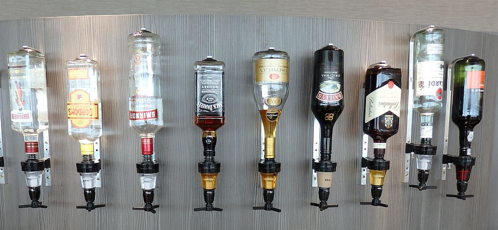 A row of 9 liquor bottles (Smirnoff, Jack Daniels, Bailey's etc.) hang upside down on a wall. Travel Risks Not Worth Taking.