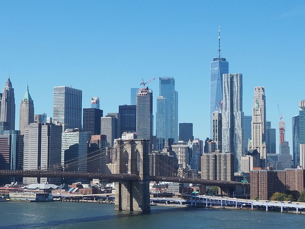 A cluster of skyscrapers with one pier of the Brooklyn bridge in the foreground.