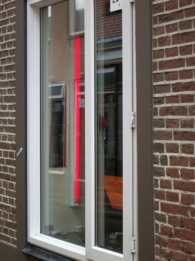 A long vertical window seen from an angle so that you can't see what's inside, except for a vertical red lamp along the side of the window.