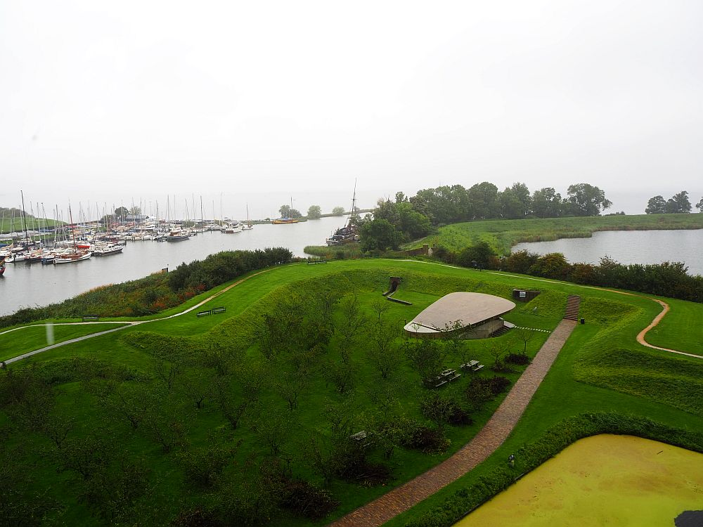 A view from Muiderslot Castle on a rainy day. In the foreground is a grassy area with squared higher areas. Beyond that on the left is a river, and cluster of sailboats on the far side. On the right a bit of another body of water is visible.
