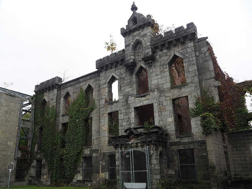 The ruin has an intact front facade but the sky is visible through the windows. Vines grow on the side and small shrubs grow here and there from the stone.