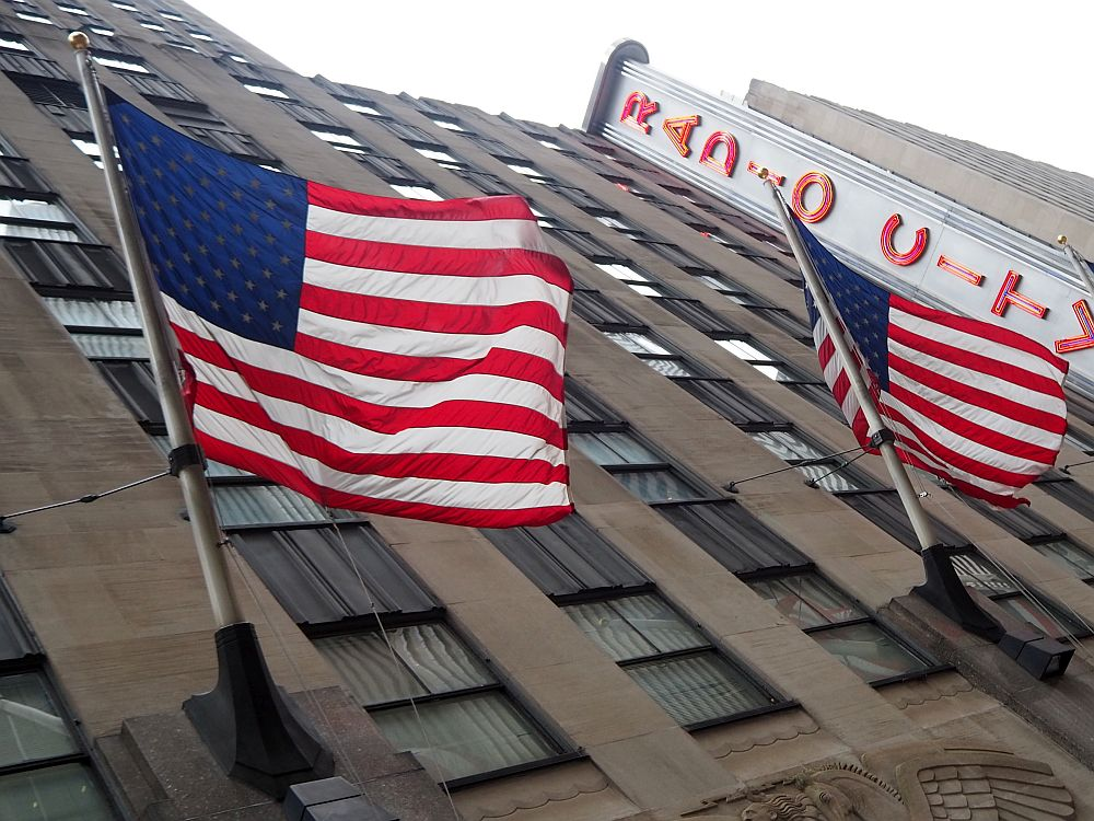 A diagonal shot looking up at Radio City Music Hall in NYC -- its sign is partly visible in the background. In the foreground is the building itself, brown stone, with two large flags waving in the wind.