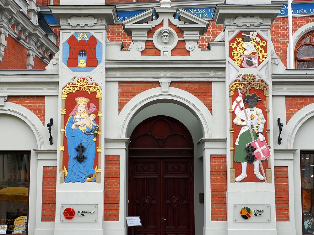 The entryway is arched with a split pediment above it. The large square columns on either side of the entryway have brightly-painted images. The one on the left is a pale-skinned Virgin Mary with a blue robe, a pink headscarf and a gold crown. She is holding a naked baby. On the right is a black man holding a red shield with a white cross and a white flag with a red cross. His pants? skirt? is green and his jacket, with looks vaguely military, is white.