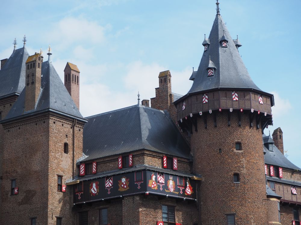 This close-up of the roof line of Castle de Haar shows two turrets. Many of the windows have shutters painted in red and white. A section below the roof has painted images between the windows as well: it looks like coats of arms and cartoon images of knights holding shields.