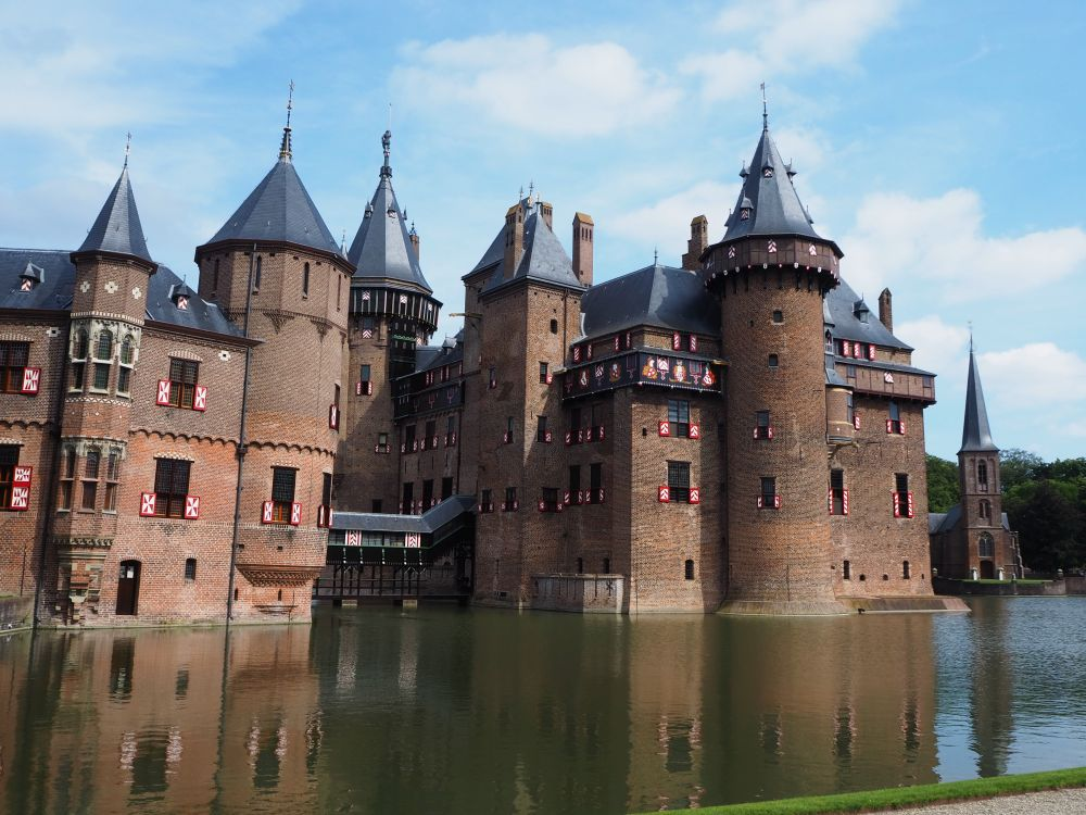 This view of Castle de Haar has about 5 turrets, not counting smalller decorative ones. Here the castle appears to rise from the water of the moat. On the right, just visible beyond the castle, is a small church with a spire in front.
