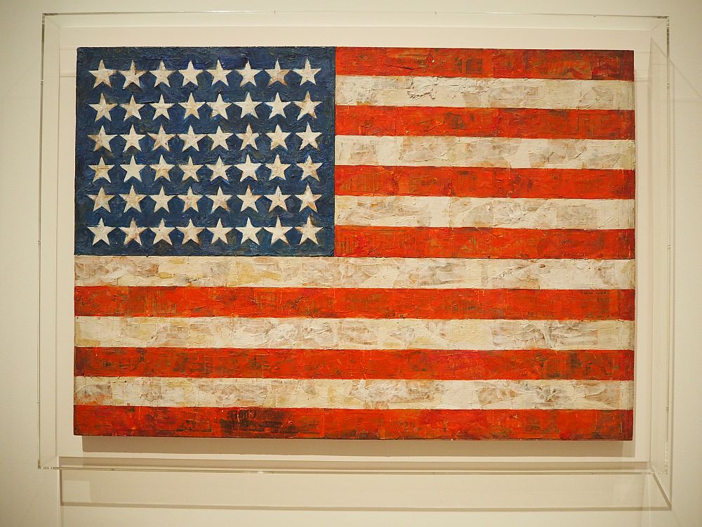 "A photo of Jasper Johns' painting called ""Flag"" at the Museum of Modern Art in NYC. It has 48 starts and more texture than an actual flag, but otherwise just looks like the flag."