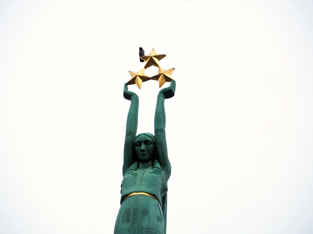 This closepup shows the green woman from the top of the monument from about the thighs up. She looks slightly downward. Her arms are extended straight up and her hands support three 5-pointed gold stars. A bird (a pigeon?) is perched on one of the top star's side points.