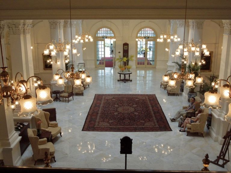 One of the Singapore film locations: the lobby of the Raffles Singapore. A view down from a floor up onto an elegant lobby: white marble floor, chandeliers, armchairs, an oriental rug in the center.