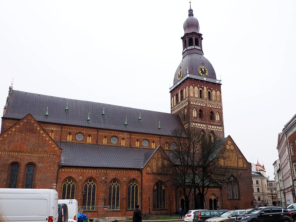 A red-brick church, seen from the side. The side has a row of gothic windows facing on to a parking lot in front. The top of the main part of the church is above that, so a row of round windows is visible above the side roof. ON the right-hand end of the church is its spire, about twice as tall as the building. It is square and has a a few rows of windows. The top of the spire has a dome with a clock and a smaller spire extending up from its middle. That littler spire has a circle of arched windows and above that is a small, elongated dome.