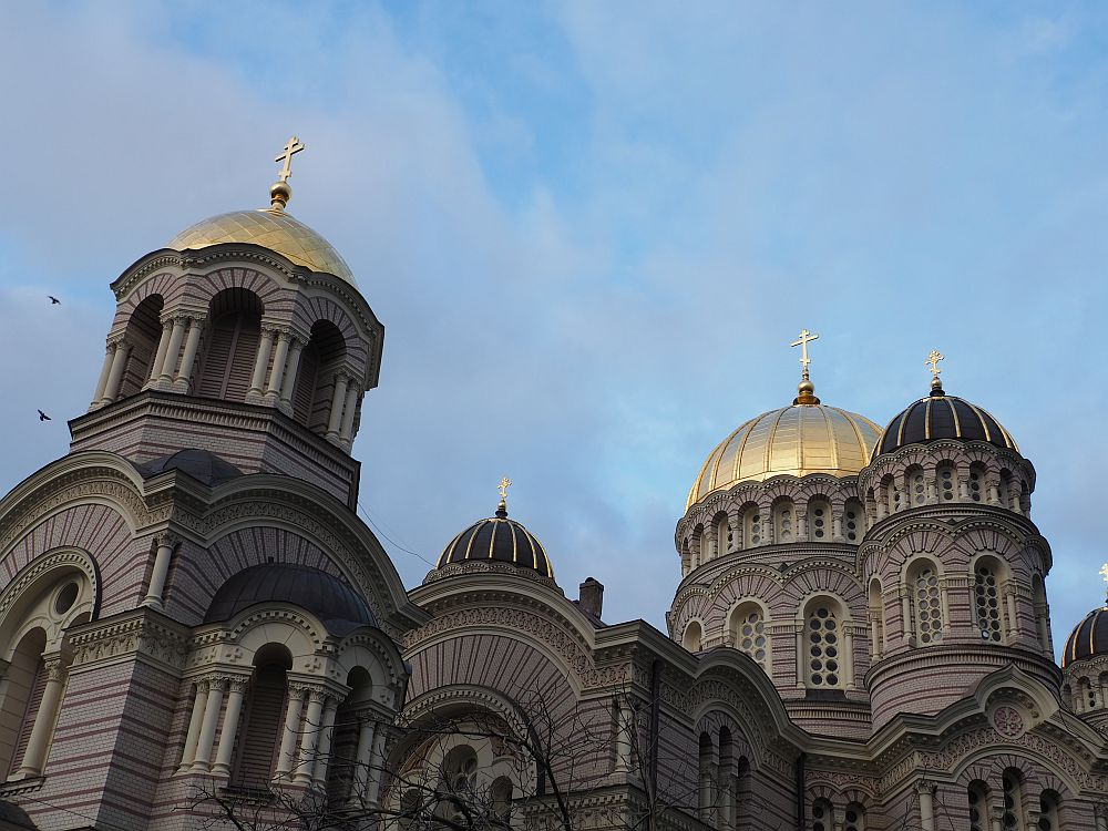 The photo shows only the top of the church: 4 1/2 domes are visible. Two of the domes are gold, while the other two smaller domes are dark green but have lines of gold on them. All are topped with gold orthodox crosses. What is visible of the building under the domes is mostly arched windows, sometimes framed by groups of small columns on either side.