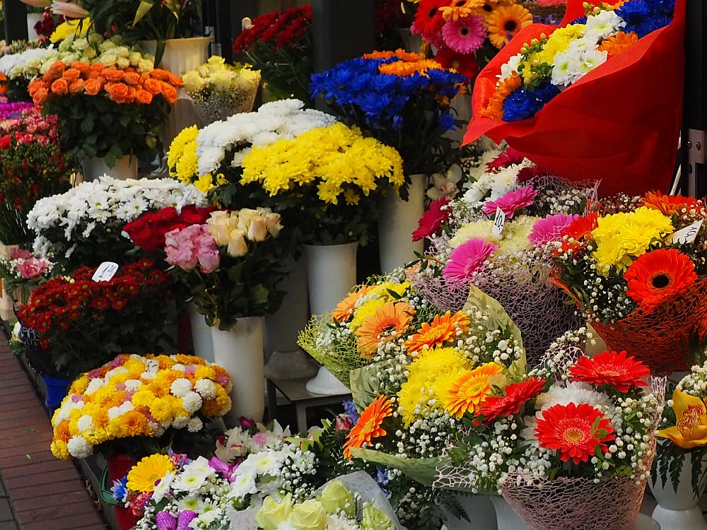 A close-up of a display of bouquets of flowers in very bright colors: pinks, reds, yellows, oranges and white primarily.