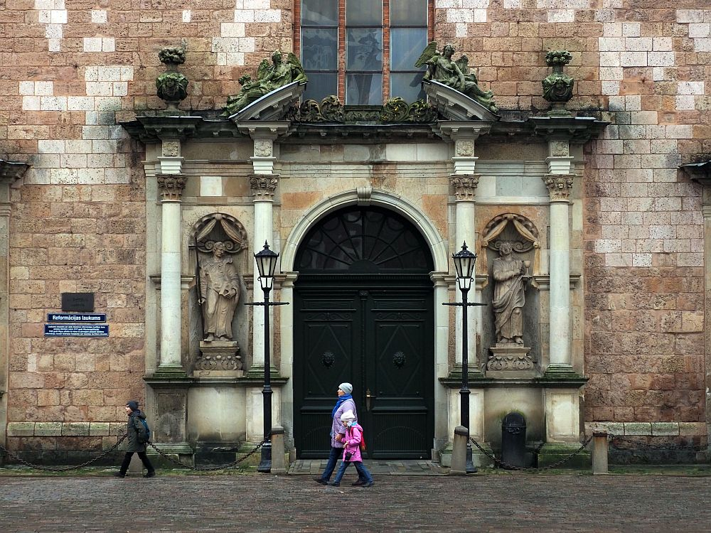 An arched entranceway with a split pediment above it, split to accommodate a large window above. On either side of the entrance is a niche with a statue in it and columns on either side of the statue. A woman and two children walk past the entrance. In terms of height, the woman's head only reaches the bottom of the statues. The wall around the entrance is old stone bricks, in shades of brown.