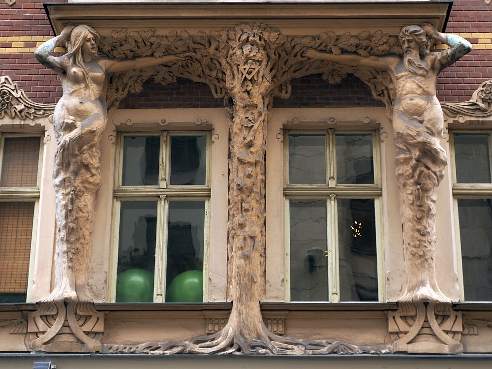This seems to be an Adam and Eve image. Eve is on the left, with a naked body to the crotch, but below that it looks more like the trunk of a tree. On the right, a male figure with a beard, also naked to the crotch and a tree trunk below that. Between them are two windows, and between the two windows is another trunk image, with roots at the bottom and what looks like vines at the top, that reach to the two human figures on either side. A masonic symbol is also visible in the center tree.