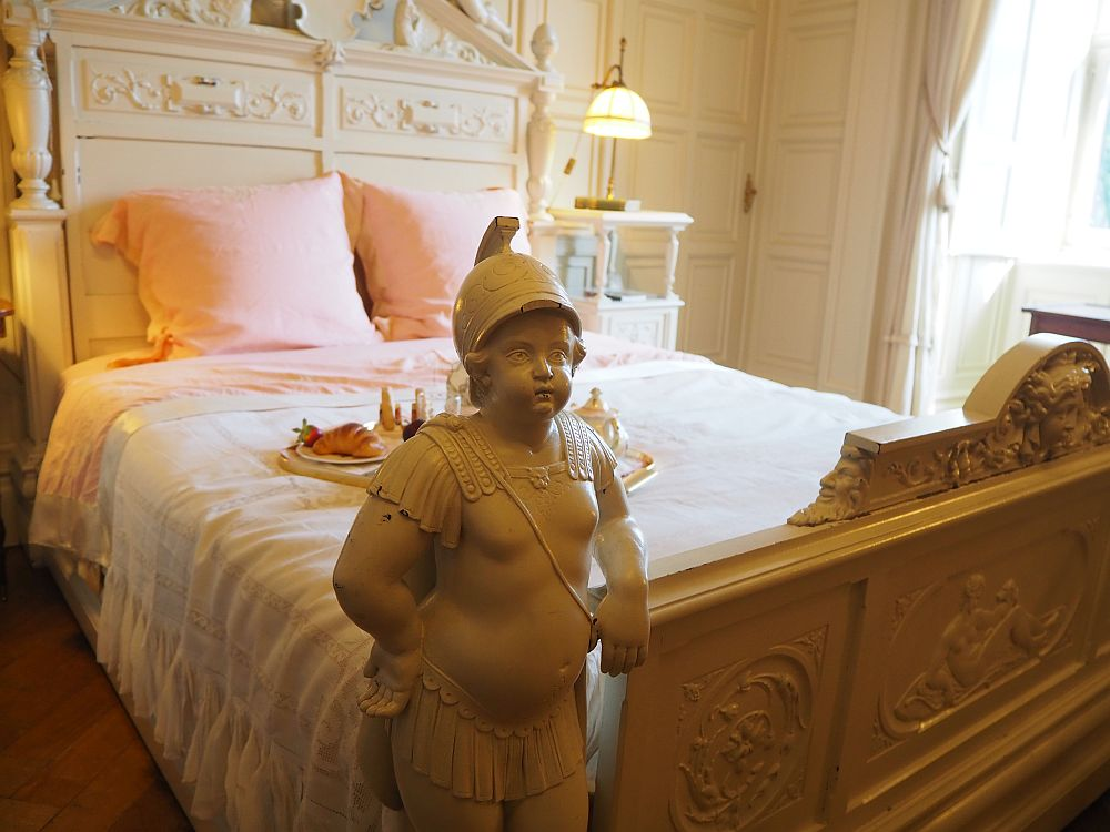A double bed made with light pink sheets. The headboard is white, carved wood. the foodboard is also carved, but here the carving extends to a complete human, child-sized, facing away from the bed. It is a rather chubby looking child wearing a roman-style helmet and a fringed skirt.