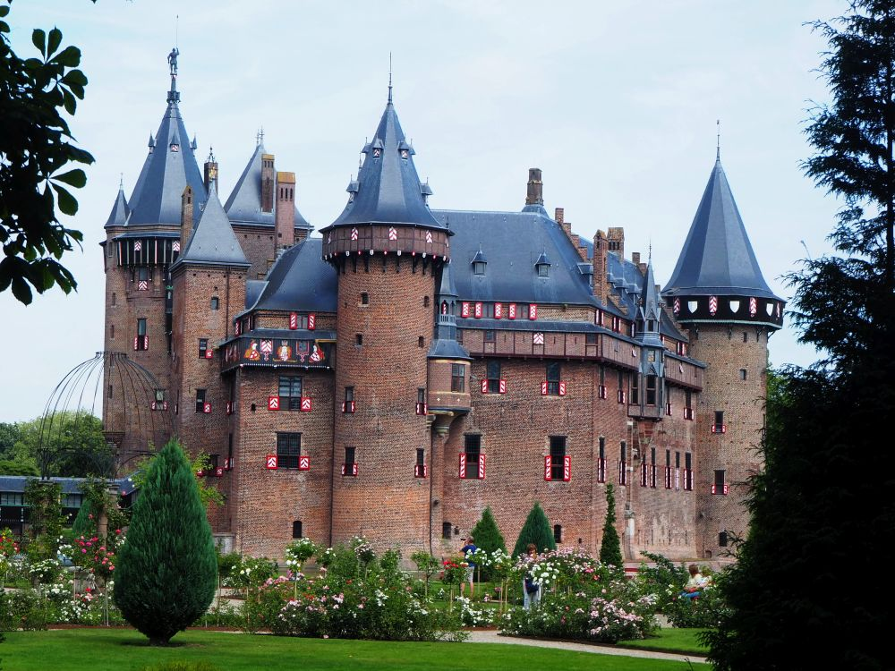 In this front view, Castle de Haar is a block of brick with steep grey roofs and red and white shutters on the small windows. While I think there are actually more,this view has 4 turreted towers and about 4 more little decorative turrets.