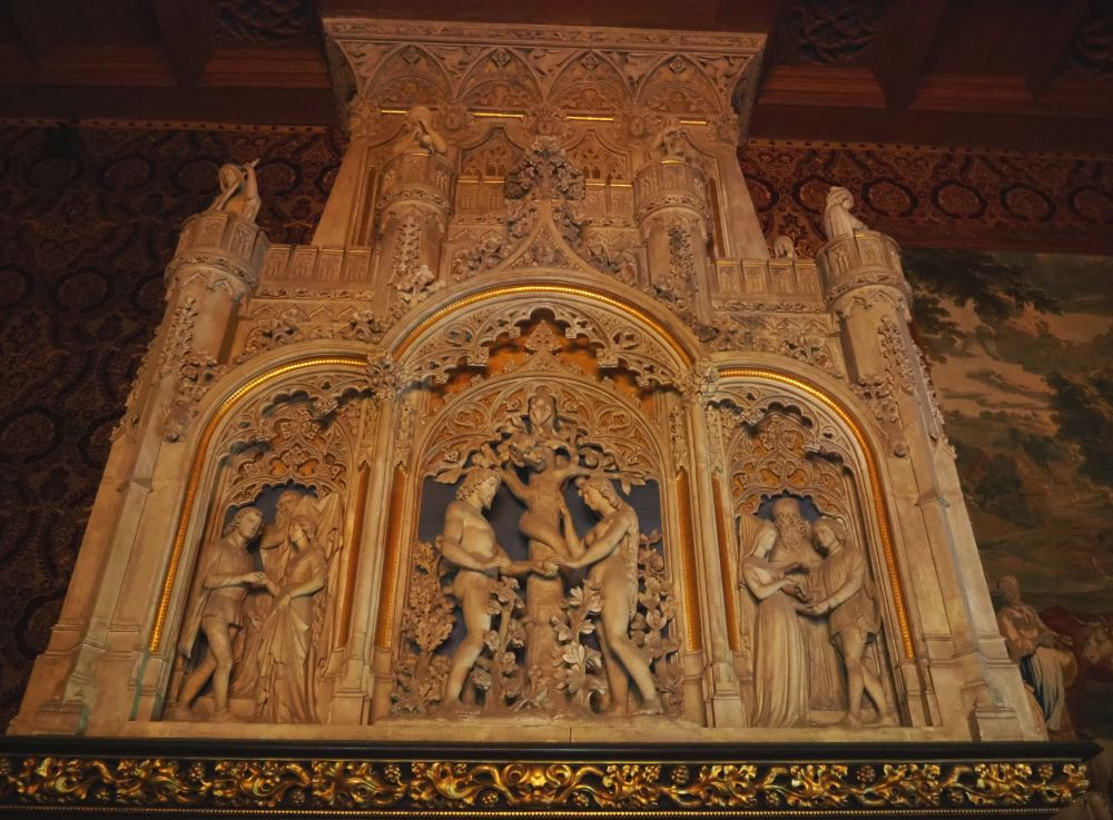 The stone fireplace is carved with three arches. In the middle is an image of Adam and Eve with a tree between them, a snake cured around its trunk. The images in the two outer arches other scenes but I can't tell what they're meant to represent. They both have figures who are dressed in medieval style. Above the arches rae more carvings, mostly flowers and leaves.