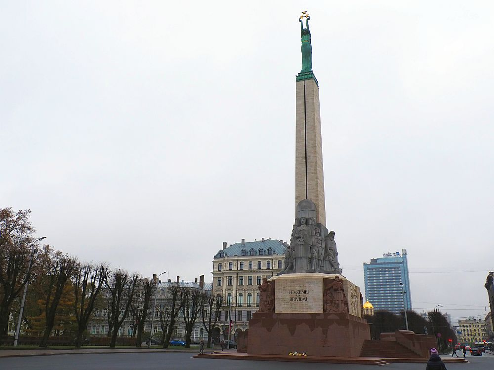 A very tall and think monument against a grey sky. The base in red stone with sculptures around the base. On the top of the base is a cluster of human figures in a grey stone. Above that is a tall, square pillar that narrows toward the top. At the top is a figure of a woman in a green tone. Her arms are extended straight above her head, holding a cluster of 3 stars in gold.