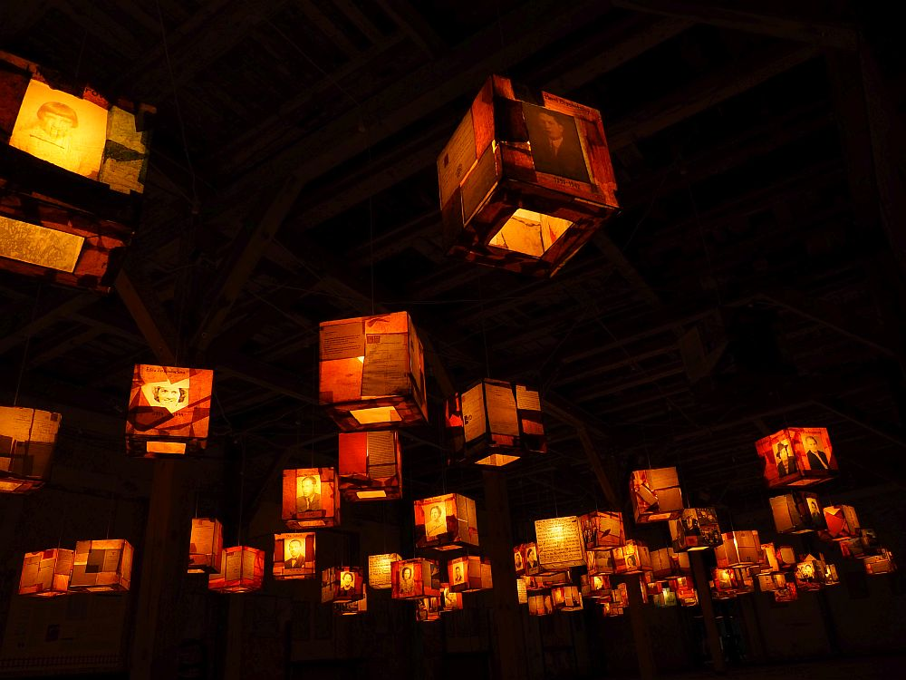 Against a black background are lit-up square lanterns, perhaps 30 or so, and pictures of people are visible on each one.