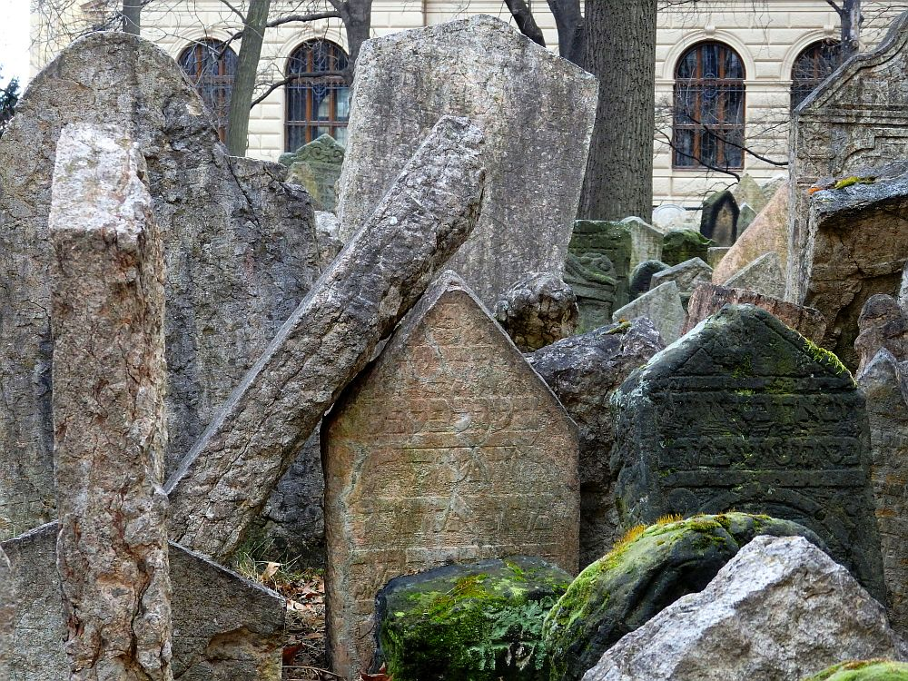 This photo shows just how close together the gravestones are: some lean against others. All are grey or brownish and a few have a bit of moss growing on them. One large one leans at a steep slant against another. Some carving is visible in Hebrew (I think).