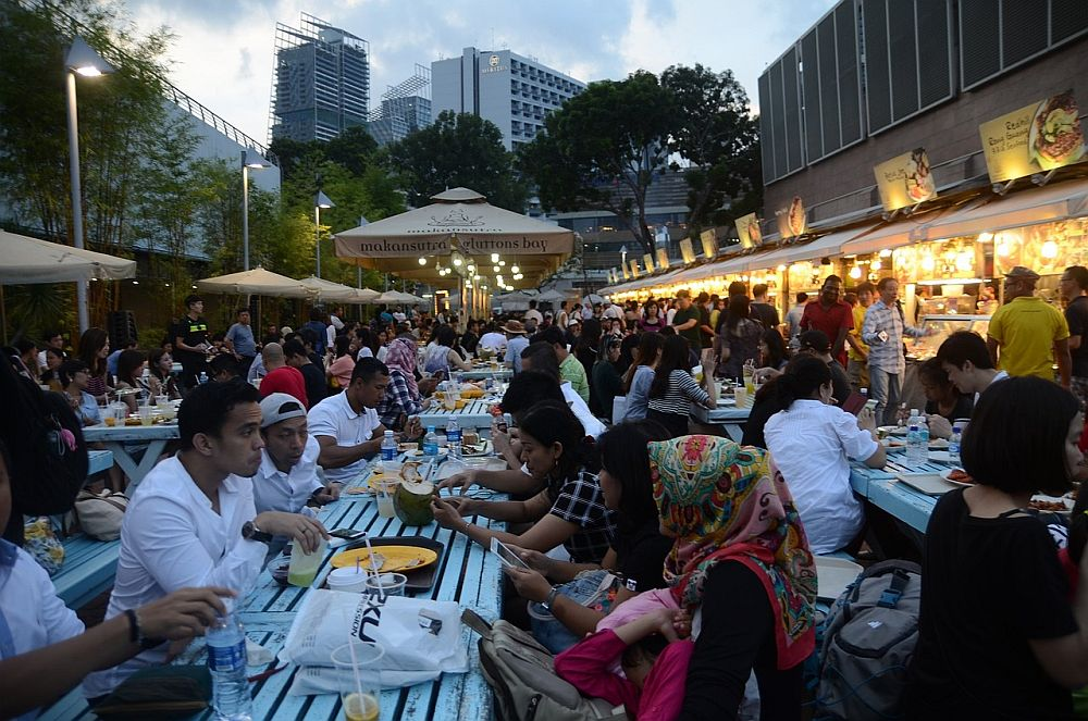 Outdoor, clearly at dusk, long lines of picnic tables, which all look completely filled up with people eating. To the right is a row of food stalls, lit brightly, and people stand waiting for their food.