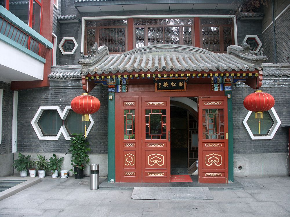 The entry is four doors wide, all painted red. A small roof juts out above it, curved in the traditional Chinese way. A red paper lamp hangs on both corners of the little roof. On each side of the entrance are six-sided windows: two on the left and one on the right.