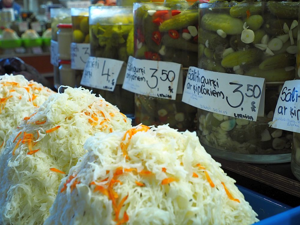 Foreground: piles of cole slaw. Background: big jars of pickles with price labels on them.