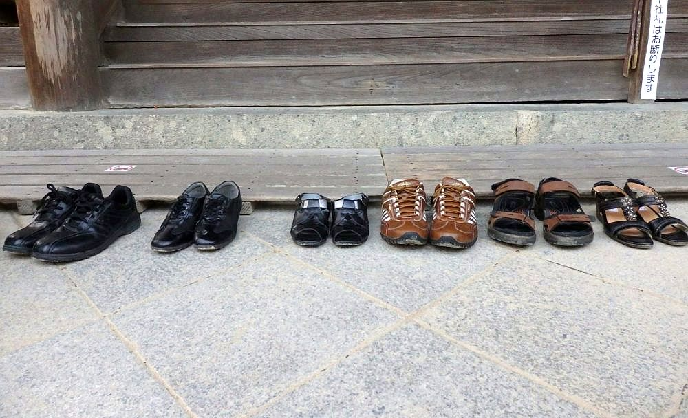 A row of 5 neatly lined-up pairs of shoes along a wall made of concrete with wood above it.