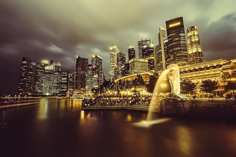 A view of the Singapore city skyline at night: a cluster of skyscrapers with some windows lit up. In the foreground is water and a merlion statue, brightly lit, pours water from its mouth into the water.