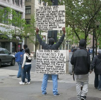 "A man stands in the middle of the sidewalk with his back to the camera. People pass on either side. The man has a sandwich board around his middle with along Bible quote in black paint on white: ""The BIble says Ecclestiates 7.20 For there is not a Just tman upon earth ... etc. Raised above his head with both arms, he holds another sign quoting Ecclesiastes 7.13 and 1.15."