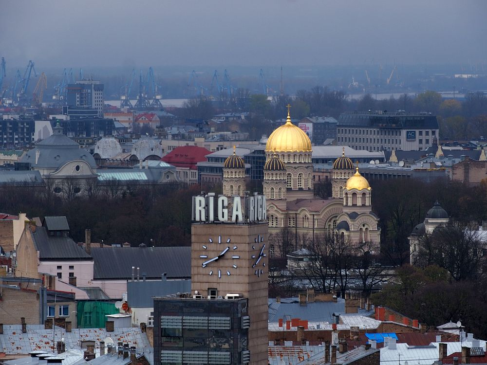 In front, a square tower with no windows but with huge signs on the two visible tops reading RIGA and, below that on the two visible sides are huge clocks. Behind that is the Russian Orthodox Church with its gold domes. In the evening light the domes seem to shine. Beyond the church is a blurry view of the city.
