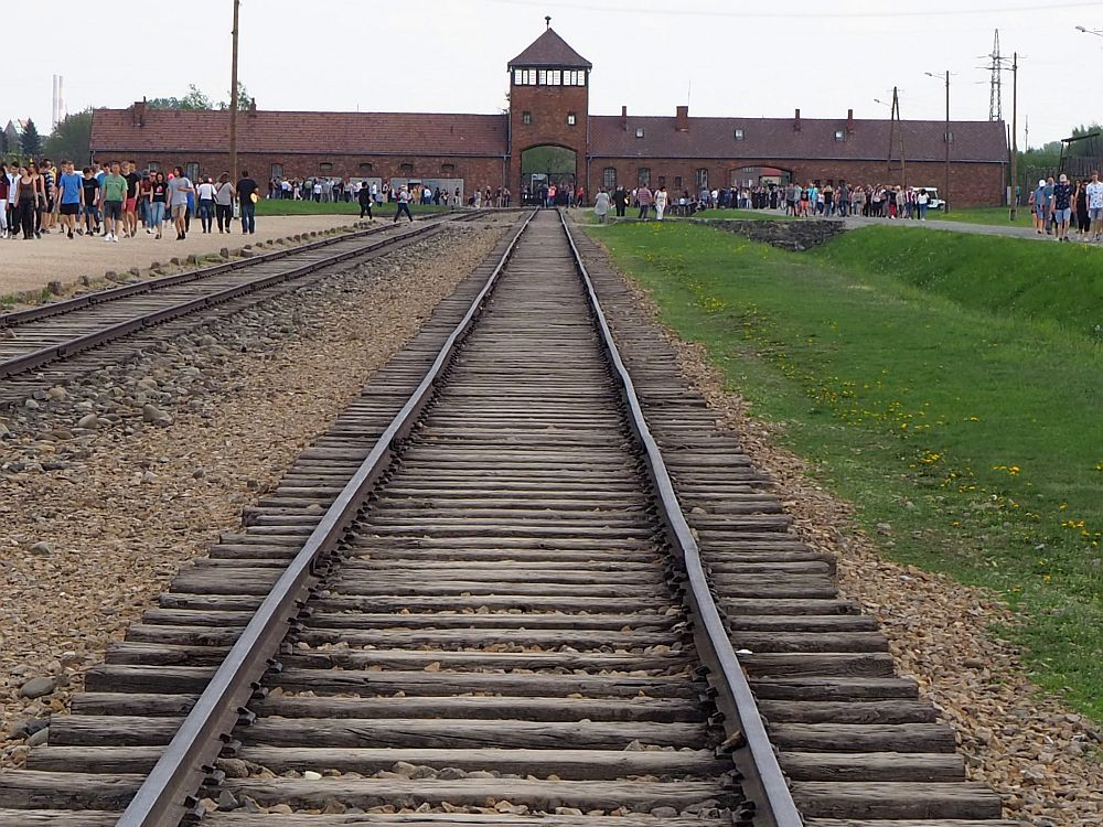 Looking down the famous train tracks toward the entranceway to Auschwitz II Birkenau. The red-brick building is long and low to the left and right, with an archway right in the center where the track enters. Above the archway is a tower with windows around the top: a guardpost. People walk on the roads on either side of the tracks.